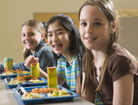 Three girls having lunch in a cafeteria.