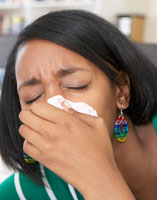 A girl coughing into a tissue.