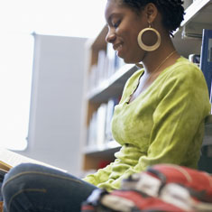 A girl leaning against a bookcase and reading