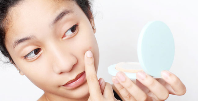 A girl examining her zit