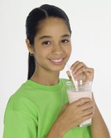 Girl drinking a glass of milk.
