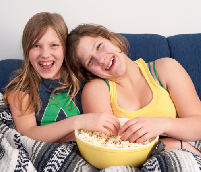 Photo of two young girls sharing popcorn.