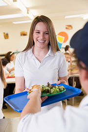 Photo of teenage girl getting food in a cafeteria.