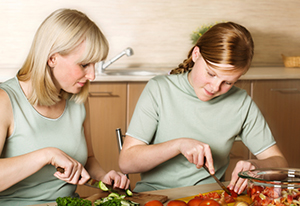 Photo of mother and daughter preparing dinner.