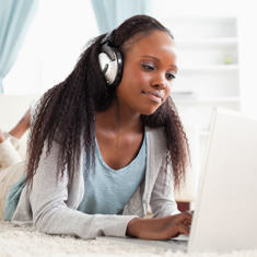 A girl on a laptop wearing headphones.
