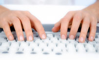 Hands typing on a keyboard.